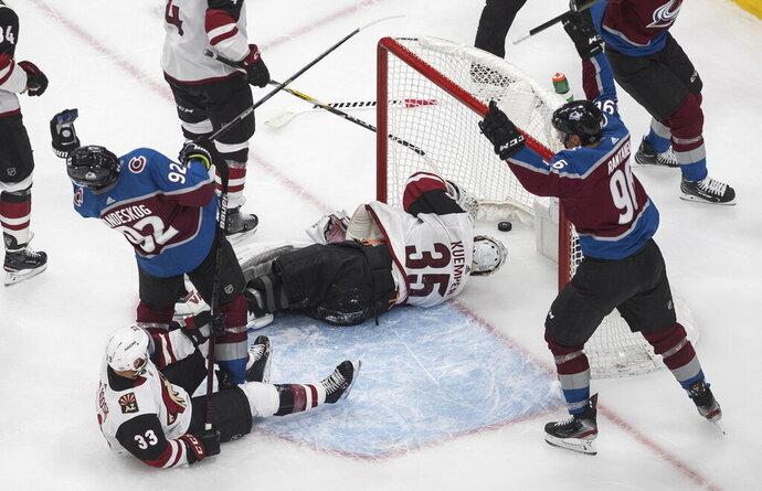 Arizona Coyotes' goalie Darcy Kuemper (35) is scored on as Colorado Avalanche's Gabriel Landeskog (92) and Mikko Rantanen (96) celebrate during the third period of a first-round NHL Stanley Cup playoff hockey game in Edmonton, Ontario, on Wednesday, Aug. 12, 2020. (Jason Franson/The Canadian Press via AP)