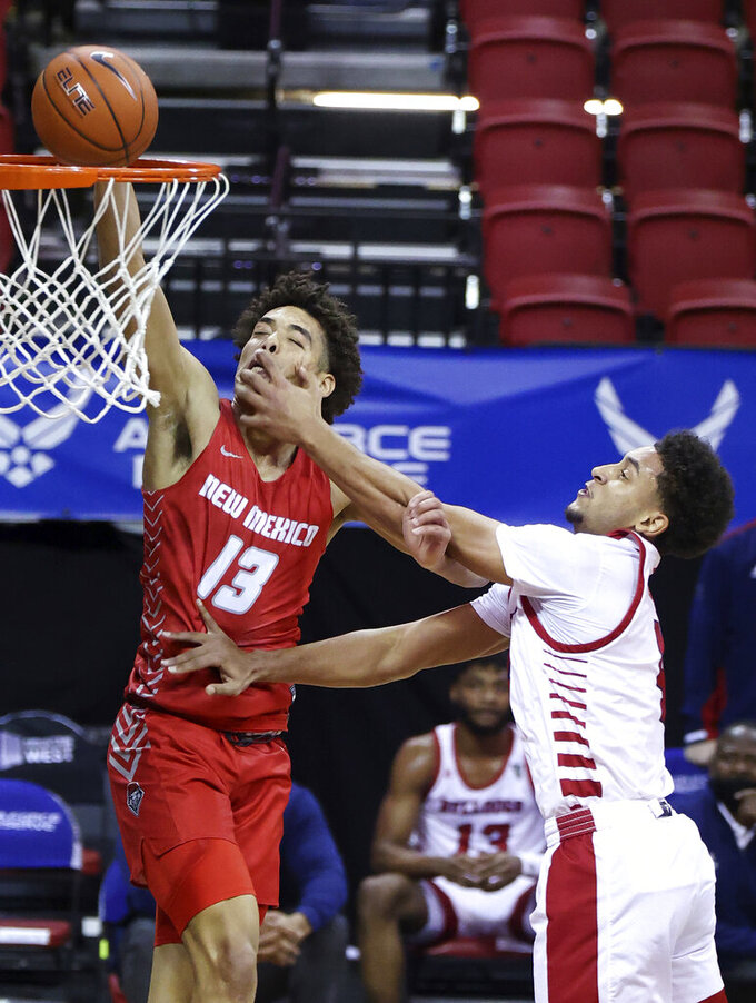 Fresno State guard Junior Ballard, right, fouls New Mexico guard Javonte Johnson on a dunk during the first half of an NCAA college basketball game in the first round of the Mountain West Conference men's tournament Wednesday, March 10, 2021, in Las Vegas. (AP Photo/Isaac Brekken)