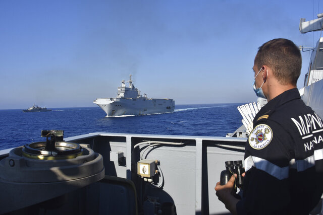 This photo provided Friday Aug.14, 2020 by the French Defense Ministry shows the French Tonnerre helicopter carrier, center, escorted by Greek and French military vessels during a maritime exercise in the Eastern Mediterranean, Thursday, Aug. 13, 2020. Greece's prime minister warmly thanked France Thursday for boosting its military presence in the eastern Mediterranean, where Greek and Turkish warships are closely shadowing each other over a Turkish energy exploration bid in waters Athens claims as its own. (French Defense Ministry via AP)