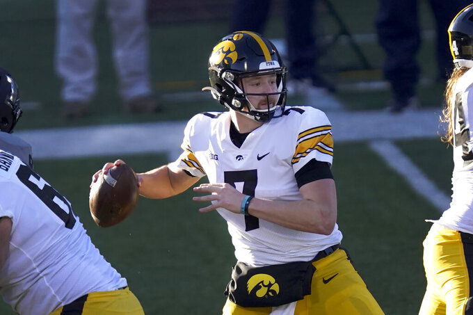 FILE - Iowa quarterback Spencer Petras sets up to pass during the first half of an NCAA college football game against Illinois in Champaign, Ill., in this Saturday, Dec. 5, 2020, file photo. Petras will be in his second year as Iowa's starter. Last season he overcame a rocky start to lead the Hawkeyes to wins in their final six games. (AP Photo/Charles Rex Arbogast, File)