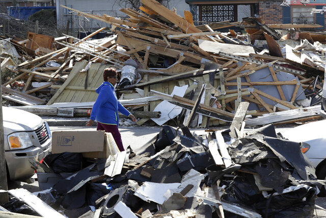 A woman walks down a street lined with debris Friday, March 6, 2020, in Nashville, Tenn. Residents and businesses face a huge cleanup effort after tornadoes hit the state Tuesday. (AP Photo/Mark Humphrey)