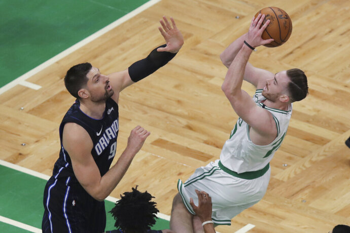 Orlando Magic center Nikola Vucevic, left, tries to stop Boston Celtics forward Gordon Hayward on a drive to the basket during the first quarter of an NBA basketball game in Boston, Wednesday, Feb. 5, 2020. (AP Photo/Charles Krupa)