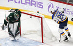 St. Louis Blues' Mackenzie MacEachern, right, scores against Minnesota Wild goalie Devan Dubnyk during the first period of an NHL hockey game Saturday, Nov. 2, 2019, in St. Paul, Minn. (AP Photo/Jim Mone)
