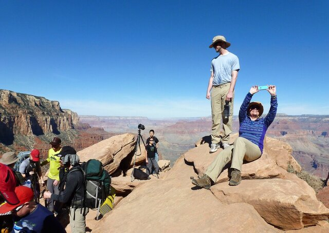 FILE - In this March 16, 2015 file photo, hikers stop and take photos along the Grand Canyon National Park's South Kaibab trail. Parks around the country are grappling with how best to expand service while preserving the pristine nature. One of the latest debates is playing out at the Grand Canyon, where park officials are road mapping future telecommunications towers. The handful that exist now are prominent among the park lodging, visitor center and residential area. (AP Photo/Anna Johnson, File)