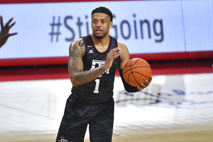 Texas A&M guard Savion Flagg (1) looks for an open man as he plays against Arkansas during the second half of an NCAA college basketball game in Fayetteville, Ark., Saturday, March 6, 2021. (AP Photo/Michael Woods)