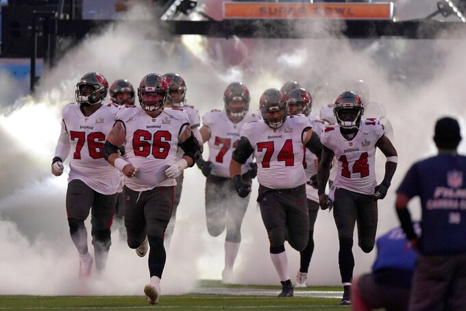 Tampa Bay Buccaneers players run onto the field for their NFL Super Bowl 55 football game against the Kansas City Chiefs, Sunday, Feb. 7, 2021, in Tampa, Fla. (AP Photo/Lynne Sladky)