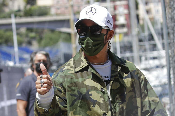 Mercedes driver Lewis Hamilton of Britain gives the thumb-up sign as he walks in the paddock at the Monaco racetrack, in Monaco, Wednesday, May 19, 2021. The Formula one race will be held on Sunday. (AP Photo/Luca Bruno)