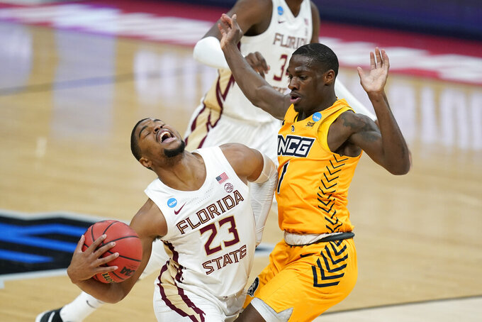 Florida State's M.J. Walker (23) goes to the basket against UNC-Greensboro's Isaiah Miller (1) during the first half of a first-round game in the NCAA men's college basketball tournament at Banker's Life Fieldhouse, Saturday, March 20, 2021, in Indianapolis. (AP Photo/Darron Cummings)