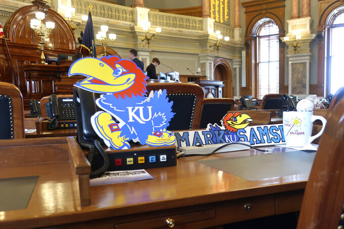 The desk of Kansas state Rep. Mark Samsel, R-Wellsville, honors University of Kansas sports teams with a sign depicting the Jayhawk mascot, Tuesday, March 10, 2020, on his House chamber desk of the Statehouse in Topeka, Kan. Kansas lawmakers are considering legislation to allow college athletes to hire agents and sign endorsement deals. (AP Photo/John Hanna)