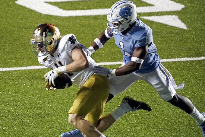 Notre Dame wide receiver Ben Skowronek (11) runs the ball while North Carolina defensive back Kyler McMichael (1) chases during the second half of an NCAA college football game in Chapel Hill, N.C., Friday, Nov. 27, 2020. (AP Photo/Gerry Broome)