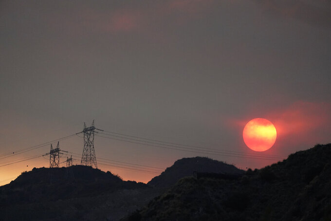 The sun sets through smoke created by the Ranch Fire, Thursday, Aug. 13, 2020, in Azusa, Calif. Heat wave conditions were making difficult work for fire crews battling brush fires and wildfires across Southern California. (AP Photo/Marcio Jose Sanchez)
