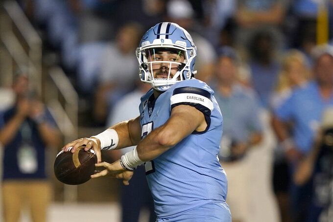 North Carolina quarterback Sam Howell looks for a receiver during the first half of the team's NCAA college football game against Virginia in Chapel Hill, N.C., Saturday, Sept. 18, 2021. (AP Photo/Gerry Broome)
