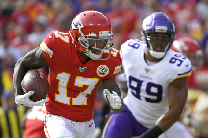 Kansas City Chiefs wide receiver Mecole Hardman (17) carries the ball in front of Minnesota Vikings defensive end Danielle Hunter (99) during the first half of an NFL football game in Kansas City, Mo., Sunday, Nov. 3, 2019. (AP Photo/Reed Hoffmann)
