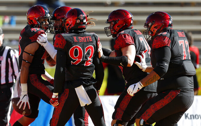 San Diego State wide receiver Jesse Matthews, far left, celebrates with teammates after scoring a touchdown during the first half of the New Mexico Bowl NCAA college football game against Central Michigan on Saturday, Dec. 21, 2019 in Albuquerque, N.M. (AP Photo/Andres Leighton)