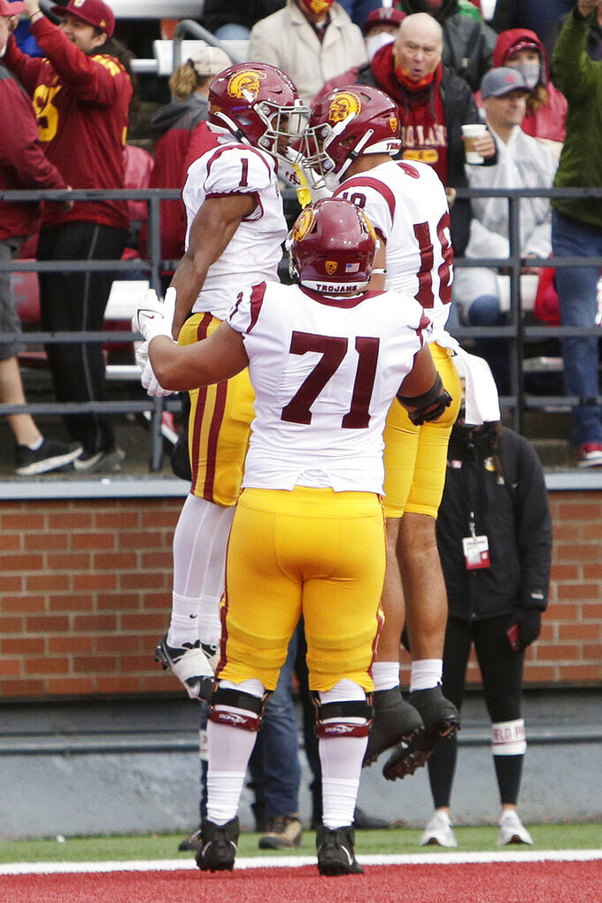 Southern California wide receiver Gary Bryant Jr. (1) celebrates his touchdown with tight end Jude Wolfe (18) and offensive lineman Liam Jimmons (71) during the second half of an NCAA college football game, Saturday, Sept. 18, 2021, in Pullman, Wash. Southern California won 45-14. (AP Photo/Young Kwak)