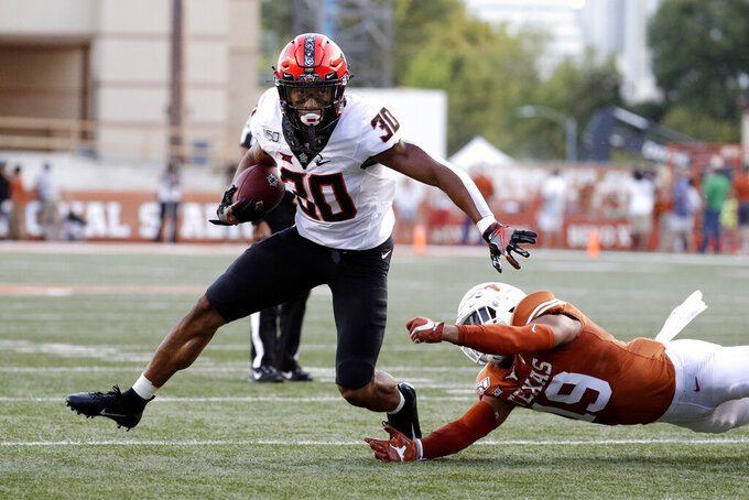 Oklahoma State running back Chuba Hubbard (30) runs past Texas defensive back Brandon Jones (19) during the first half of an NCAA college football game Saturday, Sept. 21, 2019, in Austin, Texas. (AP Photo/Eric Gay)