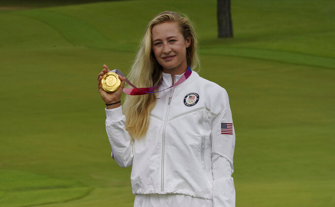 Nelly Korda, of the United States, poses with her gold medal, won in the women's golf event at the 2020 Summer Olympics, Saturday, Aug. 7, 2021, at the Kasumigaseki Country Club in Kawagoe, Japan. (AP Photo/Matt York)