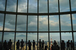 Visitors are silhouetted against a floor-to-ceiling window as they view Tokyo's skyline from an observation deck located on the top floor of Roppongi Hills Mori Tower, Thursday, Sept. 19, 2019, in Tokyo. (AP Photo/Jae C. Hong)