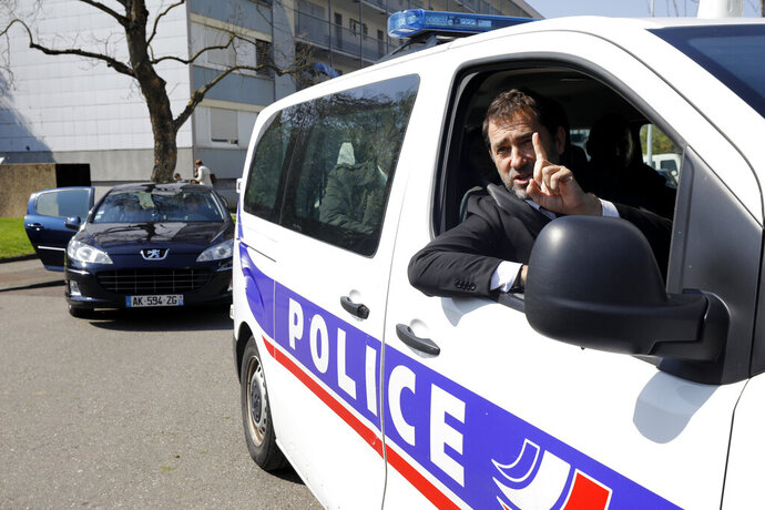 FILE - In this April 11, 2019 file photo, French Interior Minister Christophe Castaner gestures from a police car as he visits the Neuhof district of Strasbourg, eastern France. One person is in French custody on preliminary terrorism charges after threatening a Sept. 11-style plane hijacking and attack. Christophe Castaner said on France-2 television Thursday Oct. 17, 2019 night that the person was arrested Sept. 26 while