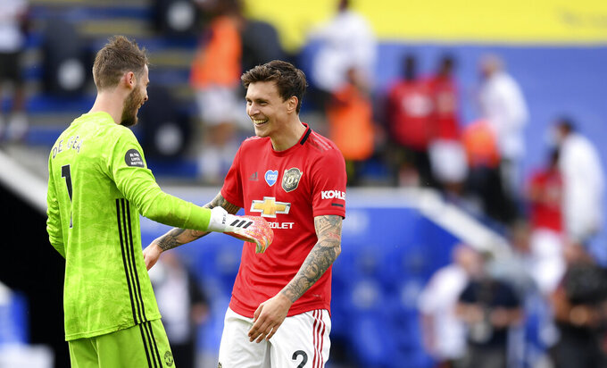 Manchester United's goalkeeper David de Gea, left, celebrates with Manchester United's Victor Lindelof at the end of the English Premier League soccer match between Leicester City and Manchester United at the King Power Stadium, in Leicester, England, Sunday, July 26, 2020. (Michael Regan/Pool via AP)