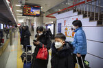 Passengers wear face masks as they wait for a train at a subway station in Beijing, Friday, Jan. 24, 2020. China broadened its unprecedented, open-ended lockdowns to encompass around 25 million people Friday to try to contain a deadly new virus that has sickened hundreds, though the measures' potential for success is uncertain. (AP Photo/Mark Schiefelbein)