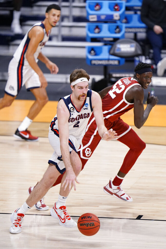 Gonzaga forward Drew Timme (2) goes around Oklahoma forward Kur Kuath (52) in the first half of a college basketball game in the second round of the NCAA tournament at Hinkle Fieldhouse in Indianapolis, Monday, March 22, 2021. (AP Photo/AJ Mast)