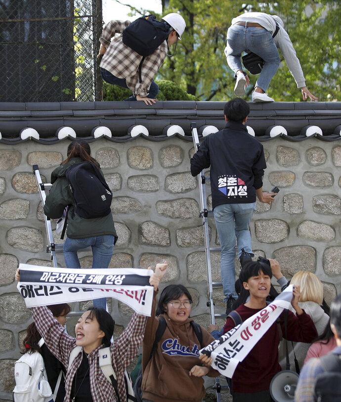 In this Friday, Oct. 18, 2019, photo, college students use ladders to climb walls of the U.S. ambassador's residence in Seoul, South Korea. South Korean police have formally on Monday, Oct. 21. arrested four anti-American students who broke into the U.S. ambassador's residence in Seoul while protesting the Trump administration's demands for South Korea to pay more to help cover the costs of keeping U.S. troops. The sign reads