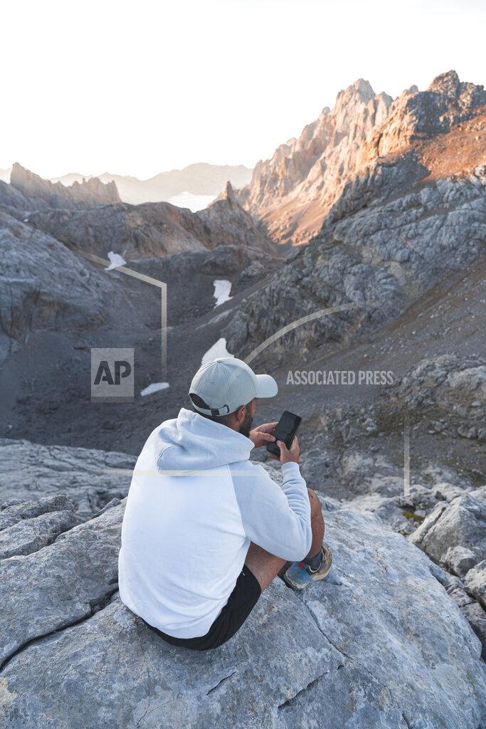 Man using smart phone on rock during sunrise, Picos de Europe, Cantabria, Spain