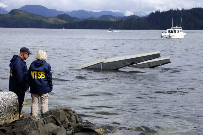 FILE - In this photo provided by the National Transportation Safety Board, NTSB investigator Clint Crookshanks, left, and member Jennifer Homendy stand near the site of some of the wreckage of the DHC-2 Beaver, Wednesday, May 15, 2019, that was involved in a midair collision near Ketchikan, Alaska, a couple of days earlier.  The pilots of two Alaskan sightseeing planes that collided in midair couldn't see the other aircraft because airplane structures or a passenger blocked their views, and they didn't get electronic alerts about close aircraft because safety systems weren't working properly. That's what the staff of the National Transportation Safety board found in their investigation. (Peter Knudson/NTSB via AP)