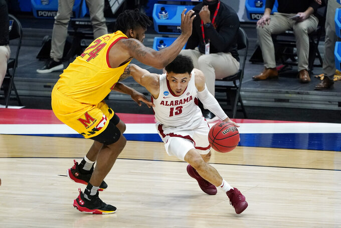 Alabama's Jahvon Quinerly (13) drives against Maryland's Donta Scott (24) during the first half of a college basketball game in the second round of the NCAA tournament at Bankers Life Fieldhouse in Indianapolis Monday, March 22, 2021. (AP Photo/Mark Humphrey)