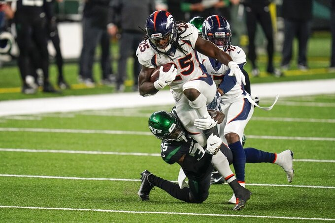 Denver Broncos running back Melvin Gordon (25) is tackled by New York Jets' Pierre Desir (35) during the first half of an NFL football game Thursday, Oct. 1, 2020, in East Rutherford, N.J. (AP Photo/Seth Wenig)