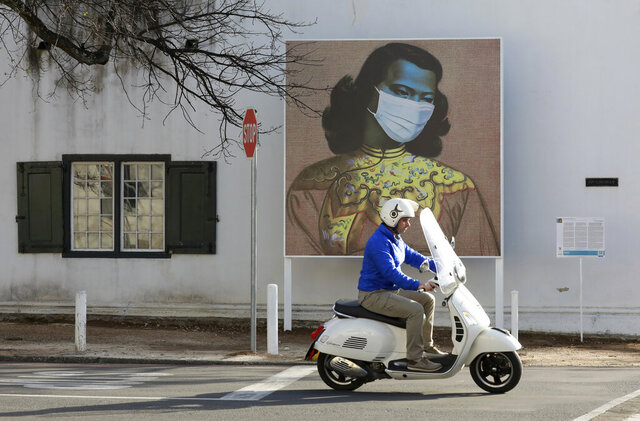 A man rides his scooter in front of a marked version of Vladimir Tretchikoff's