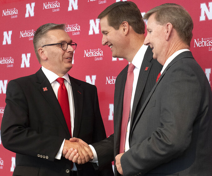 University of Nebraska Chancellor Ronnie Green, left, shakes hands with Trev Alberts, center, as NU President Ted Carter looks on during a during a news conference where Alberts was introduced as Nebraska's new athletic director, Wednesday, July 14, 2021, at Memorial Stadium in Lincoln, Neb. (Gwyneth Roberts/Lincoln Journal Star via AP)