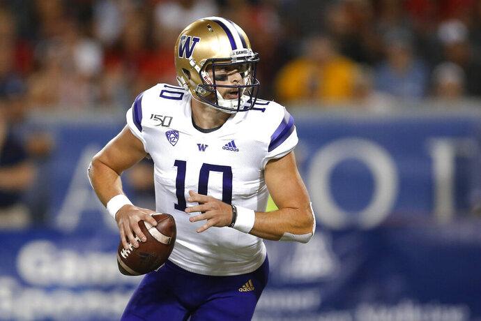 Washington quarterback Jacob Eason looks for a receiver during the first half of the team's NCAA college football game against Arizona on Saturday, Oct. 12, 2019, in Tucson, Ariz. (AP Photo/Rick Scuteri)