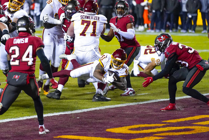 Washington Football Team running back J.D. McKissic (41) dives in to score a touchdown against the Tampa Bay Buccaneers during the first half of an NFL wild-card playoff football game, Saturday, Jan. 9, 2021, in Landover, Md. (AP Photo/Julio Cortez)
