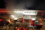 Firefighters work to control a fire at a warehouse owned by the national film institute, Cinemateca, which houses South America's largest collection of films, in Sao Paulo, Brazil, Thursday, July 29, 2021. Sao Paulo's fire department said 15 fire vehicles and 50 firefighters were at the site working to prevent the flames from spreading to a larger area of the building. (Ronaldo Silva/Futura Press via AP)