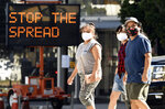 FILE - Pedestrians wear masks as they walk in front of a sign reminding the public to take steps to stop the spread of coronavirus, Thursday, July 23, 2020, in Glendale, Calif. After weeks of stressing education over enforcement, California communities say they are now issuing fines and relying on anonymous tips to make sure businesses and residents are complying with health orders requiring masks, disinfection, and social distancing as the state tries to contain the coronavirus.  (AP Photo/Chris Pizzello, File)