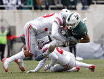 FILE - In this Nov. 10, 2018, file photo, Michigan State receiver Cody White, right, is stopped by Ohio State's Malik Harrison during the first quarter of an NCAA college football game, in East Lansing, Mich. (AP Photo/Al Goldis)