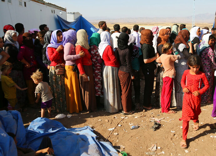 FILE - In this Aug. 12, 2014 file photo, displaced Iraqis from the Yazidi community gather for humanitarian aid at Nowruz camp, in Derike, Syria. On Tuesday, Nov. 26, 2019, a survivor of the mass slaughter of the Yazidi minority in Iraq five years ago has told the U.N. Security Council that he still hears his brothers and nephews calling his name before they were killed by Islamic State extremists. (AP Photo/ Khalid Mohammed, File)