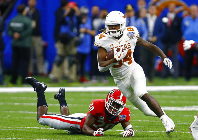 Texas wide receiver Lil'Jordan Humphrey (84) carries past Georgia defensive back J.R. Reed (20) on a pass reception in the first half of the Sugar Bowl NCAA college football game in New Orleans, Tuesday, Jan. 1, 2019. (AP Photo/Butch Dill)