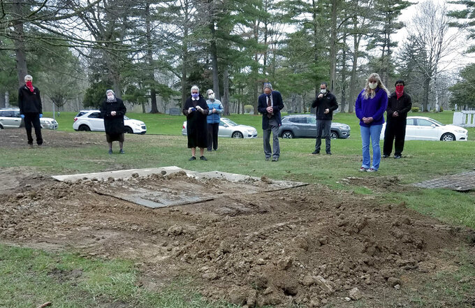 In this April 24, 2020, photo provided by Sister Mary Alfonsa Van Overberghe, nuns from a convent in Livonia, and others gather at the burial site of one of 13 nuns who have died from the coronavirus in the Michigan city. (Sister Mary Alfonsa Van Overberghe via AP)