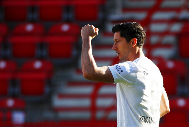 Robert Lewandowski of Munich celebrates his side's opening goal during the German Bundesliga soccer match between Union Berlin and Bayern Munich in Berlin, Germany, Sunday, May 17, 2020. The German Bundesliga becomes the world's first major soccer league to resume after a two-month suspension because of the coronavirus pandemic. (AP Photo/Hannibal Hanschke, Pool)