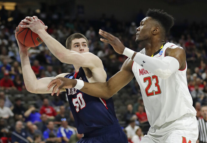 Belmont 's Seth Adelsperger, left, looks to shoot against Maryland 's Bruno Fernando (23) during the first half of a first round men's college basketball game in the NCAA Tournament  in Jacksonville, Fla., Thursday, March 21, 2019. (AP Photo/John Raoux)
