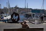 A man sits on a bench during a hot day in Marseille's Old Port, southern France, Friday Aug. 7, 2020. France has warned the public to prepare for a heatwave as temperatures were set to rise to 42 degrees Celsius (107 Fahrenheit) in parts of the country. (AP Photo/Daniel Cole)