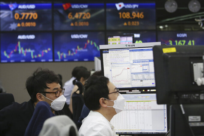 Currency traders watch monitors at the foreign exchange dealing room of the KEB Hana Bank headquarters in Seoul, South Korea, Friday, April 30, 2021. Asian shares were mostly lower Friday amid uncertainty about the prospects for a gradual global economic recovery from the coronavirus pandemic. (AP Photo/Ahn Young-joon)