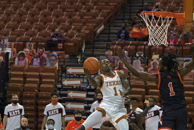 Texas guard Andrew Jones, left, drives against Sam Houston State forward Manny Crump, right, during the first half of an NCAA college basketball game, Wednesday, Dec. 16, 2020, in Austin, Texas. (AP Photo/Michael Thomas)
