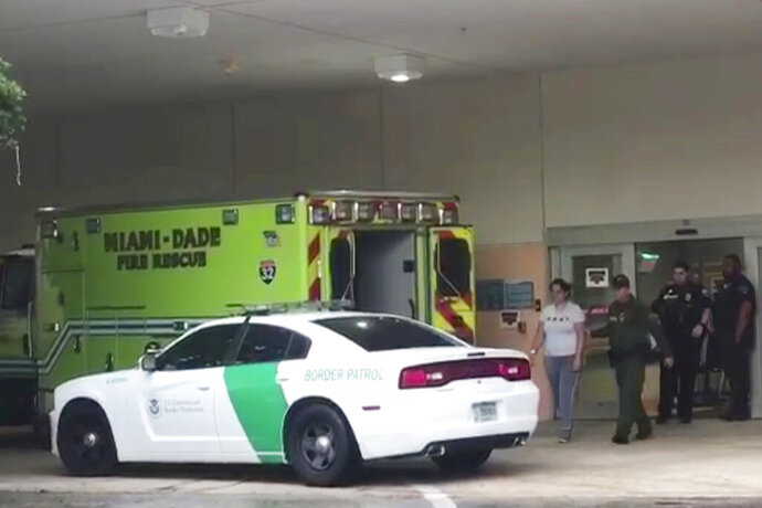 In this image taken from video provided by the Florida Immigrant Coalition, a border patrol agents escorts a woman to a patrol car Sunday, Oct. 13, 2019, at Aventura Hospital in Aventura, Fla. The woman had been detained by border patrol agents, when she fell ill. The agent took her to the hospital emergency room for treatment. The presence of immigration authorities is becoming increasingly common at health care facilities around the country, and hospitals are struggling with where to draw the line to protect patients' rights amid rising immigration enforcement in the Trump administration. (Florida Immigrant Coalition via AP)
