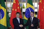 China's President Xi Jinping, left, and Brazil's President Jair Bolsonaro, pose for photos shaking hands at the end of their statements during a bilateral meeting on the sidelines of the 11th edition of the BRICS Summit, at the Itamaraty Palace, in Brasília, Brazil, Wednesday, Nov. 13, 2019. (AP Photo/Eraldo Peres)