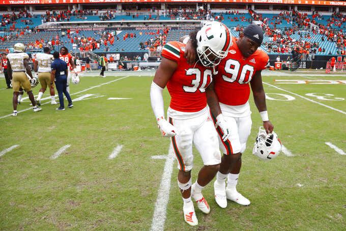 Miami defensive lineman Tyreic Martin (90) consoles linebacker Romeo Finley (30) as they walk off the field after an NCAA college football game against Georgia Tech, Saturday, Oct. 19, 2019, in Miami Gardens, Fla. Georgia Tech defeated Miami 28-21 in overtime. (AP Photo/Wilfredo Lee)