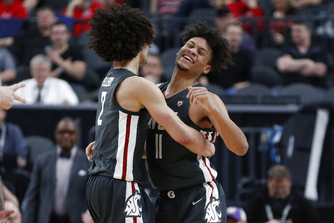 Washington State's CJ Elleby, left, and DJ Rodman celebrate after a play against Colorado during the second half of an NCAA college basketball game in the first round of the Pac-12 men's tournament Wednesday, March 11, 2020, in Las Vegas. (AP Photo/John Locher)